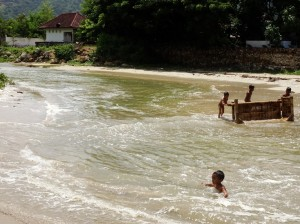 Kids playing where the utterly befouled river discharges into the sea