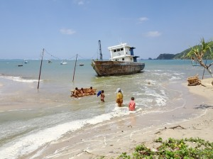 Kids playing, woman crossing and stranded boat