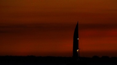 Dark sail against a red sky